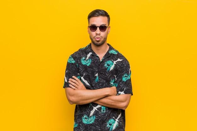 Молодой человек в летней одежде дует в щеки, усталое выражение лица