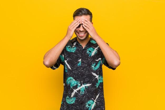 夏服を着た若い男が目を覆っている手、広く驚きを待っている笑顔