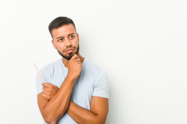 Молодой южно-азиатский мужчина держит зубную щетку, глядя в сторону с сомнительным и скептическим выражением лица