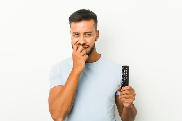 Молодой южноазиатский мужчина держит телевизионный контроллер, кусая ногти, нервный и очень взволнованный