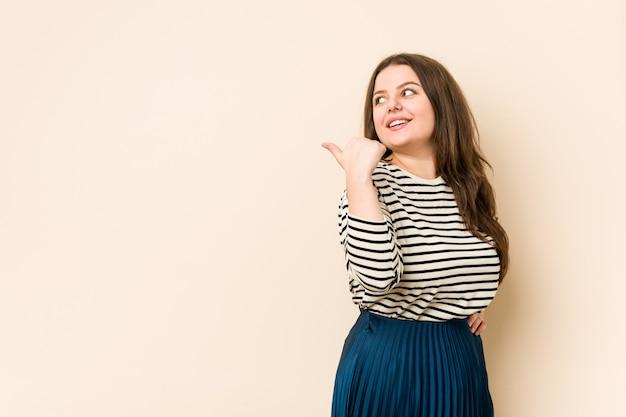 親指の指を離れて、笑いと屈託のない若い曲線の女性ポイント