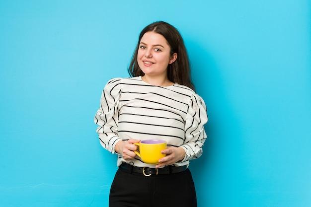 幸せ、笑顔、陽気な茶マグカップを保持している若い女性