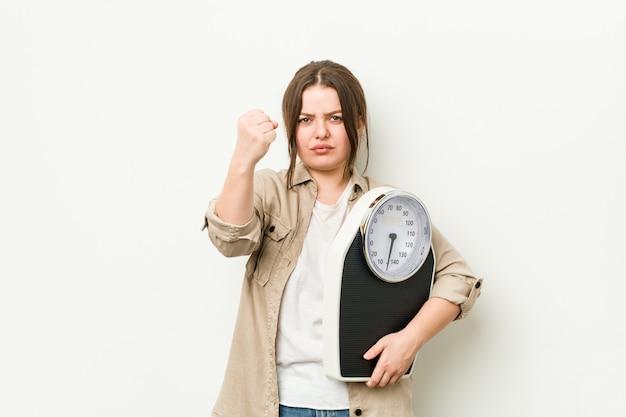 Молодая соблазнительная женщина держит в руках кулак