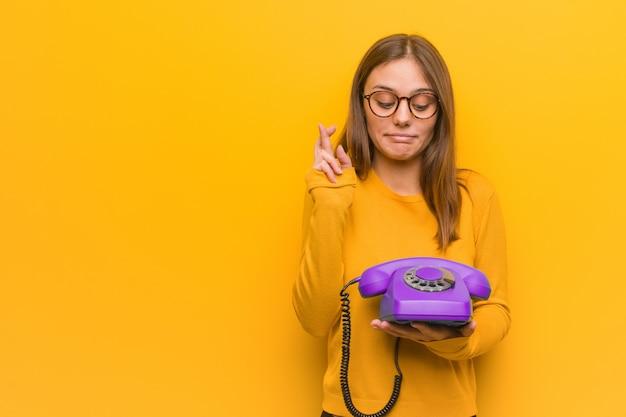 彼女はビンテージの電話を持っている幸運を持っていることのための指を交差若いきれいな女性