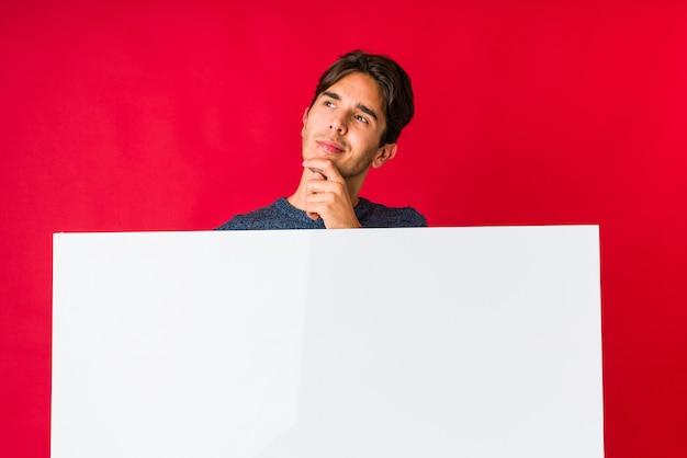 疑いと懐疑的な表情で横に見ているプラカードを保持している若い男
