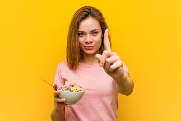 Молодая женщина, держащая миску каши, показывая номер один с пальцем