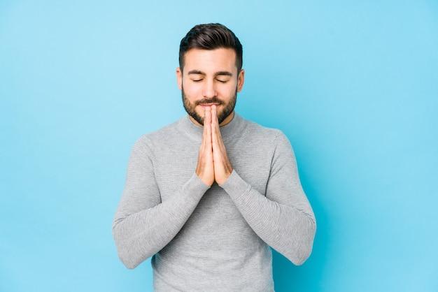 口の近くに祈って手を繋いでいる若い男は自信を持って感じています