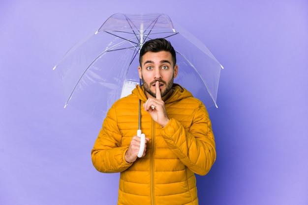 秘密を保つ傘を保持している若いハンサムな男