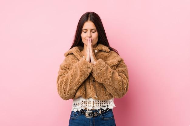 口の近くに祈って手を繋いでいる若いかわいい女性は自信を持って感じています
