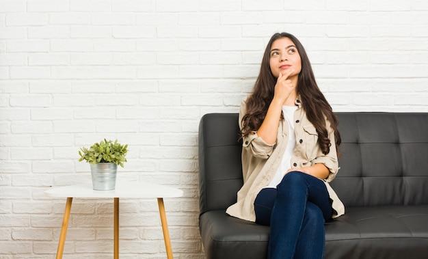 疑わしいと懐疑的な表情で横に見ているソファーに座っていた若い女性