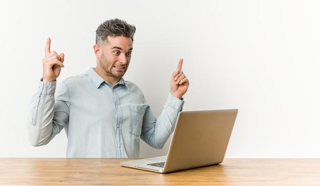 彼のラップトップで働く若いハンサムな男は、空白のスペースを見せて両指で示しています。
