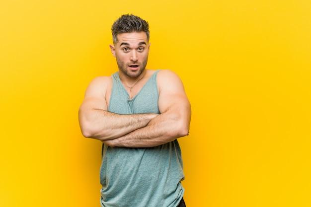 自信を持って、決意で腕を組んでいる黄色の壁に対して若いフィットネス男。