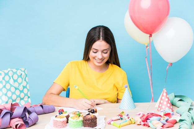 Молодая кавказская женщина подготавливая вечеринку по случаю дня рождения