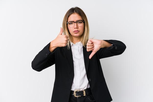 親指アップと親指ダウンを示す若いビジネス白人女性