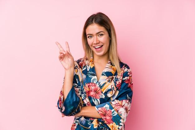 指で平和のシンボルを示すうれしそうな屈託のないパジャマを着ている若い白人女性。