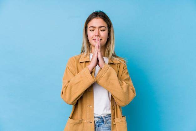 口の近くで祈って手を繋いでいる若い白人女性は自信を持って感じています。