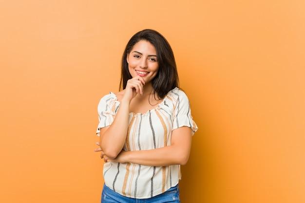幸せと自信を持って、手であごに触れる笑顔若い曲線の女性