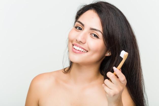 歯ブラシを保持している若い美しい、自然なヒスパニック系女性のクローズアップ