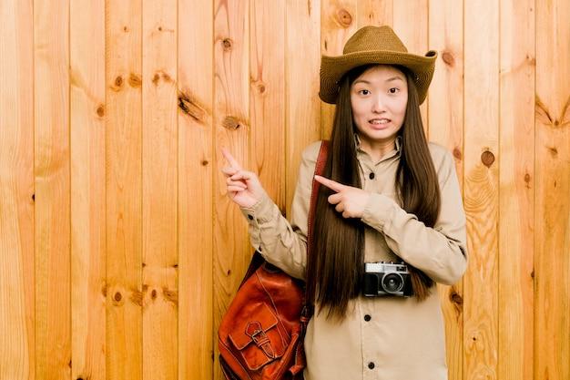 若い旅行者女性人差し指で指しているショックを受けた