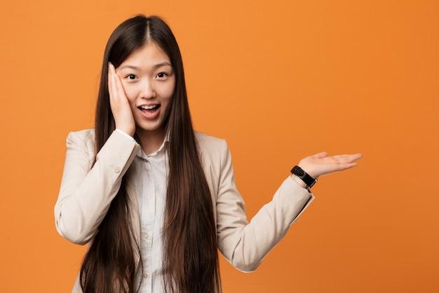 Молодая бизнес-леди держит что-то на ладони