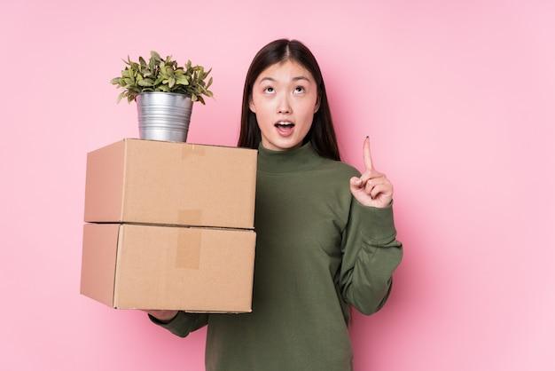 開いた口で逆さまに指しているボックスを保持している若い女性