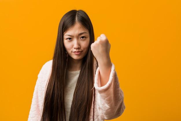 Молодая женщина в пижаме показывает кулак