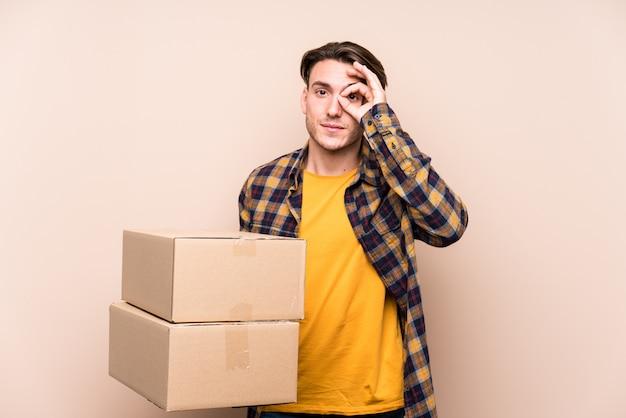 Молодой человек, держащий коробки взволнован, держа хорошо жест на глаз