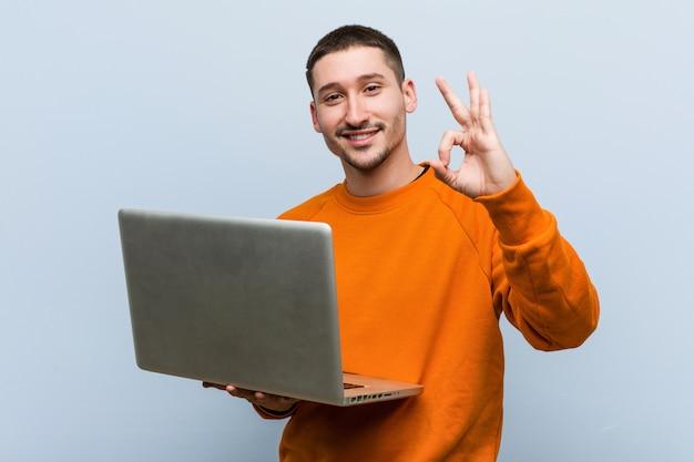 Молодой человек держит ноутбук веселый и уверенный, показывая ок жест
