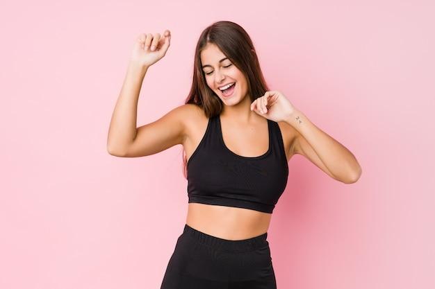 特別な日を祝うスポーツを行う若い白人フィットネス女性ジャンプし、エネルギーで腕を上げます。