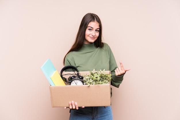 Молодая женщина кавказской, переезда в новый дом, указывая пальцем на вас, как будто приглашая подойти ближе.