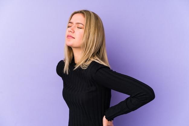 背中の痛みに苦しんでいる若い金髪白人女性。