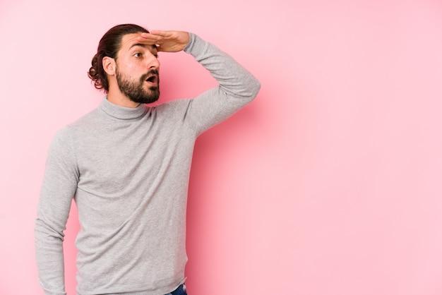 額に手をつけて遠くを見てピンクの壁に若い長い髪の男。