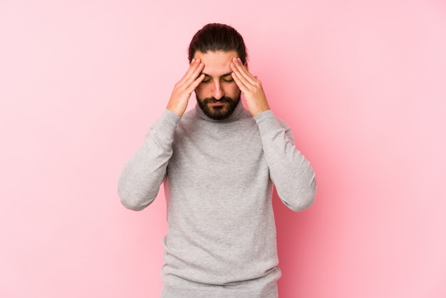 寺院に触れると頭痛を持つピンクの壁に若い長い髪の男。