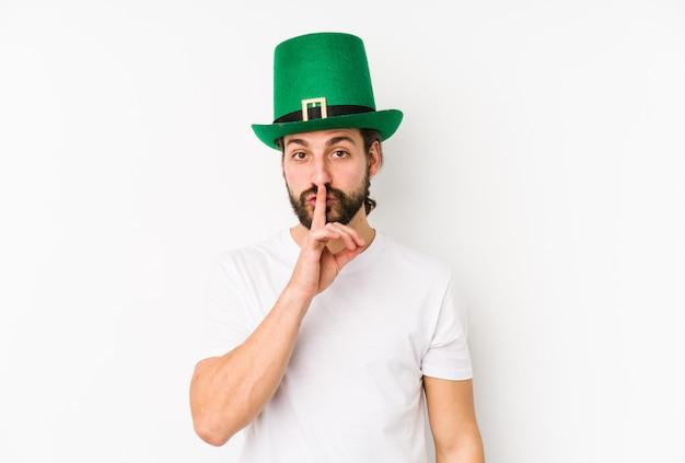 聖パトリックの帽子をかぶって、秘密を守ったり沈黙を求めたりする若い白人男性。