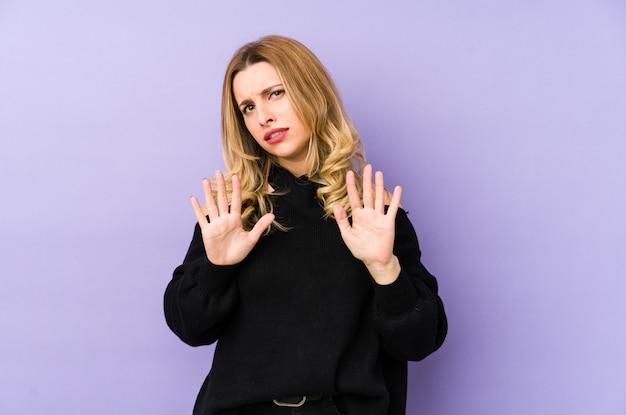 Молодая блондинка отвергает кого-то, показывая жест отвращения