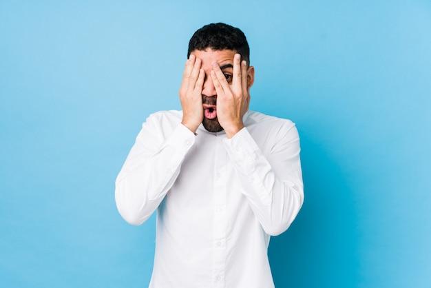 Молодой латинский мужчина моргает сквозь пальцы испуганно и нервно