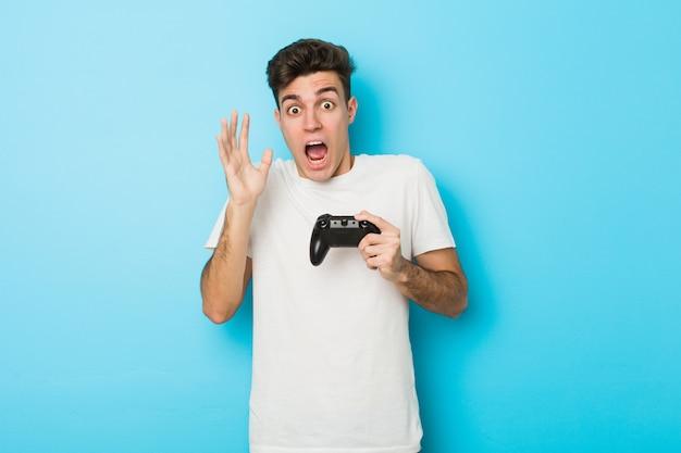 Молодой человек играет в видеоигры с игровым контроллером, празднует победу или успех