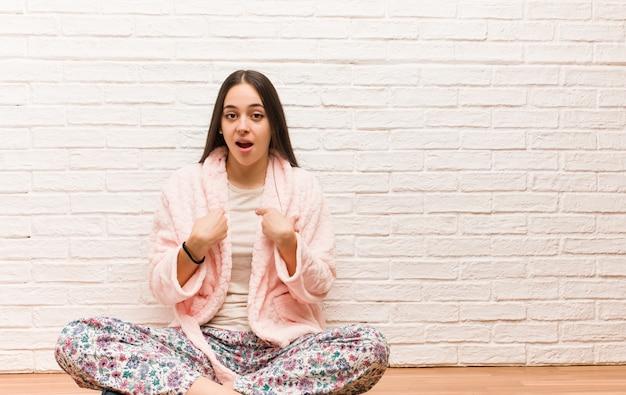 パジャマを着た若い女性が驚いた、成功と繁栄を感じる