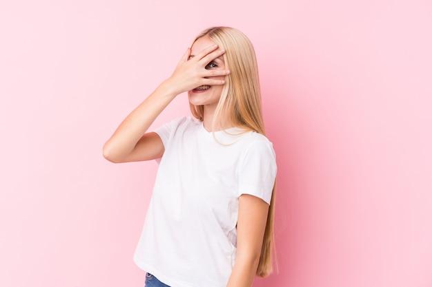 Молодая блондинка моргает сквозь пальцы, смущенно закрывая лицо