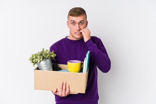 若い男が爪をかむ新しい家に移動し、神経質で非常に不安