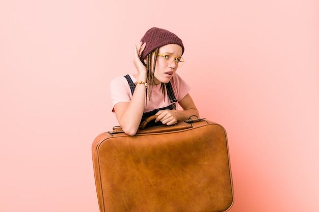 Молодая женщина, держащая чемодан пытается слушать сплетни