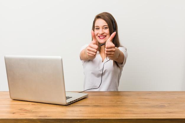 Молодая телемаркетер женщина с пальцами поднимает, ура о чем-то