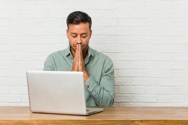 口の近くで祈って手を繋いでいる彼のラップトップで座っている若いフィリピン人男性は自信を持って感じています。