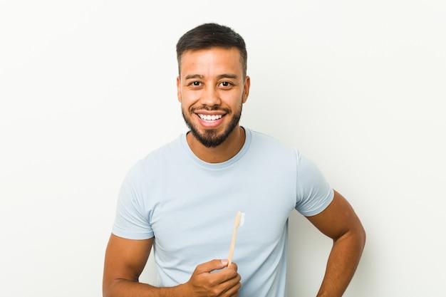 Молодой южноазиатский человек, держащий зубную щетку, смеющуюся и весело проводящую время.