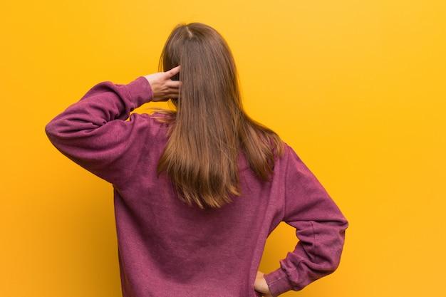 Молодая случайная женщина сзади думая о чем-то