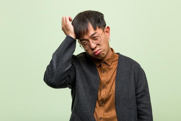 緑の壁に対して若いアジア人