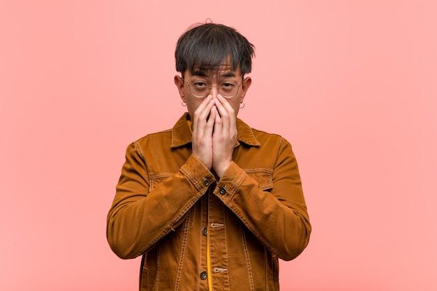 非常に怖がって、隠されていることを恐れてジャケットを着ている若いアジア人