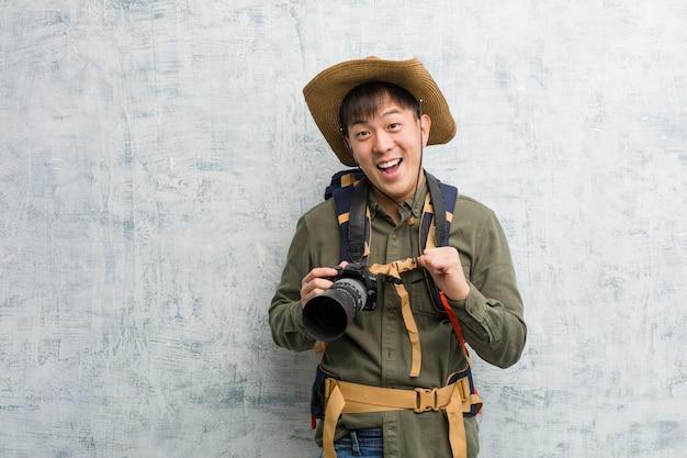 Молодой азиатский исследователь человек держит камеру удивлен, чувствует себя успешным и процветающим