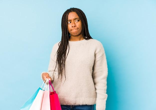 混乱しているショッピングバッグを保持している若い女性は、疑いと不安を感じる