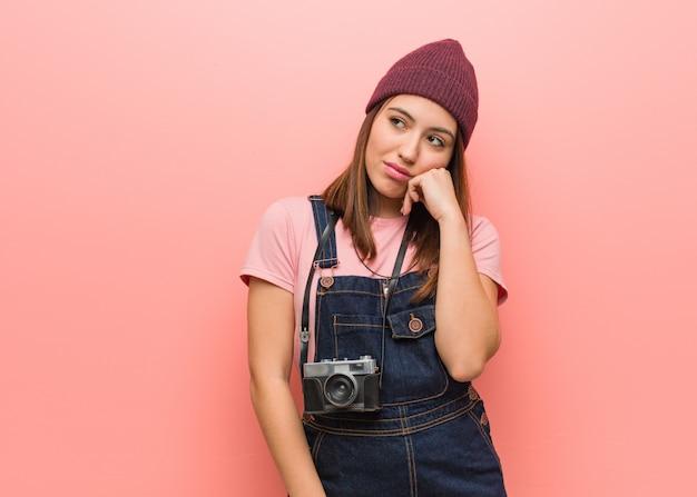Молодой милый фотограф женщина думает о чем-то, глядя в сторону